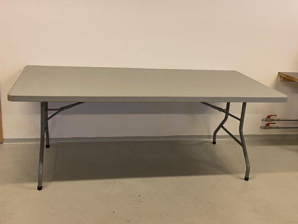 Billedet viser et hvidt plastikbord med stålstel. Det er et 76×180 cm bord