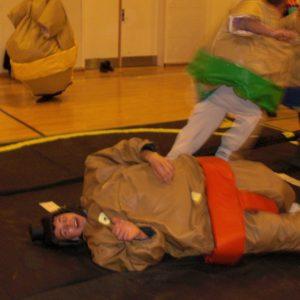 Her ses sumodragter udlejning med to personer der slåsser. De er begge iført en sumodragt og har et hhv. rødt og grønt billede på.