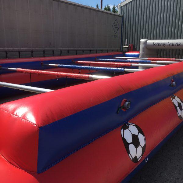 Oppustelig bordfodbold i rød og blå med fodbold på siden