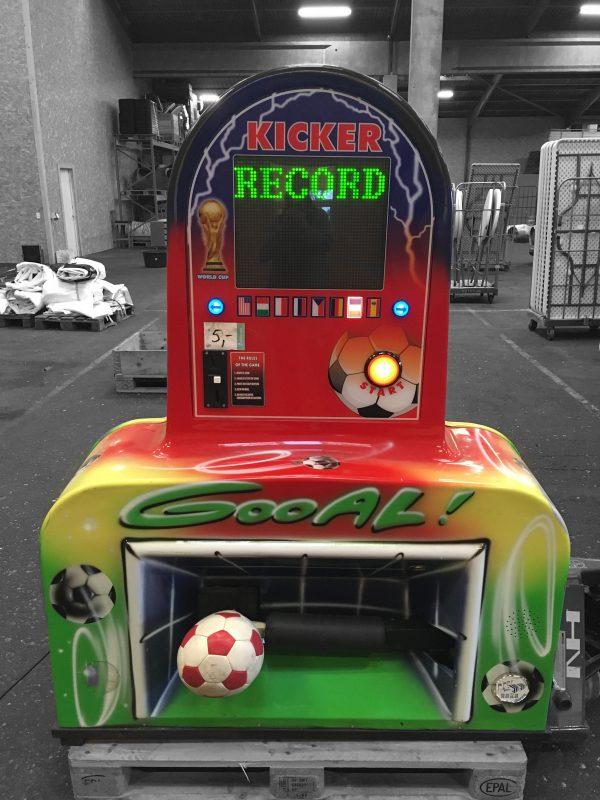 Fodbold sparker maskine ses her i rød, grøn og gul og med en fodbold på vej op i krydset på et mål. Der er også en måler med, som måler hastigheden på sparket.