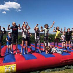 På billedet ses en hoppepude i rød og blå med en masse glade børn på.